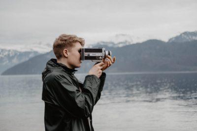 Man looking through retro video camera